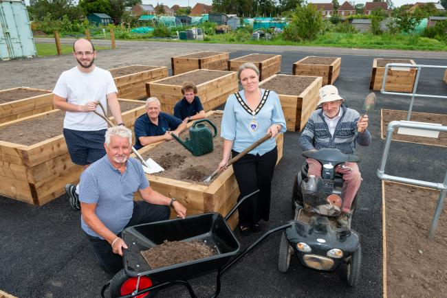 Town Mayor Councillor Michelle Molloy with Councillor Tandy, members of the Amenity team and the Allotments Association holding gardening tools in front of an accessible plot