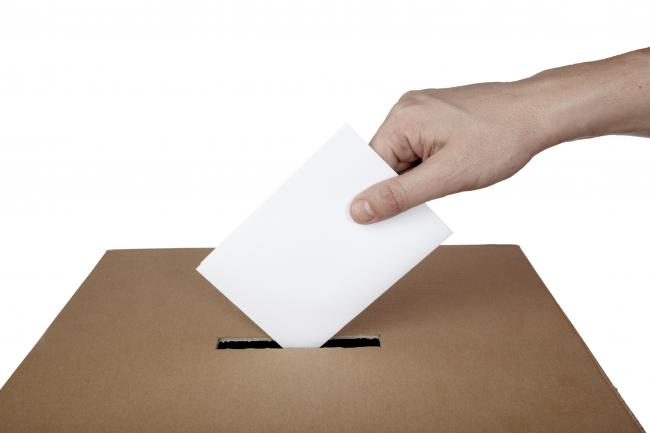 Ballot box with hand placing in vote