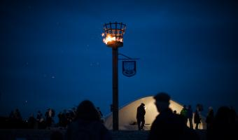 Lit beacon with people walking past
